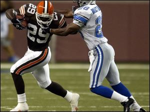 Browns back James Jackson, who had 41 yards on six carries, tries to get away from Lions safety Bracey Wright.