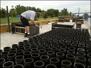 Bob Smith, vice president of Colonial Fireworks of Clayton, Mich., prepares some of the nearly 3,000 mortar tubes that would come into play during the finale of the Toledo fireworks display along the Maumee River in International Park.