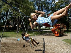 Chelsey Gray, in polka dots, and Ashlee Hartsfeld have fun on swings that often break down.