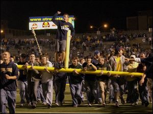 University of Toledo students carry off a goal post after the final gun made the Rocket upset over Pittsburgh official.