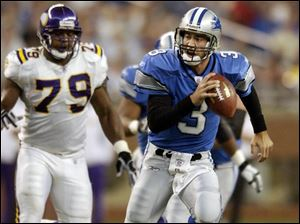 Detroit quarterback Joey Harrington, right, is forced to scramble as Minnesota defensive end Kenny Mixon gives chase.