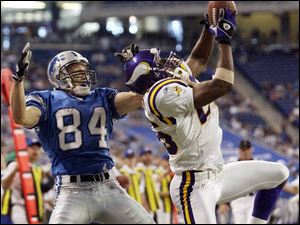 Minnesota's Denard Walker, right, picks off a pass by Detroit's Joey Harrington in the end zone in the game's final minute, one of three interceptions for the Vikings.