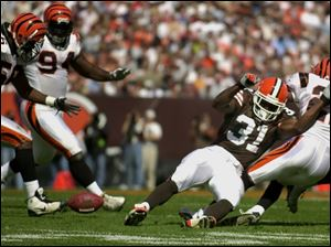 Cleveland's William Green fumbles after a hit by Cincinnati's Jeff Burris, right. The Browns' Jeff Faine recovered, but other mistakes could not be overcome as Cleveland fell to 1-3