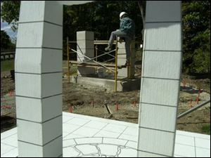 Sculpture technician Mike Barker is framed by a model of the memorial. The local chapter of the Ancient Order of the Hibernians initiated the $40,000 project.