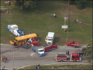 Emergency crews get the children off the bus after it collided with the tractor-trailer rig Oct. 10, 2002, while on its way to an outing at Erie Orchards & Cider Mill.