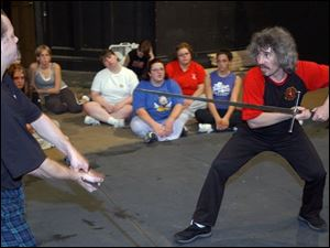 John Lennox, left, acts as a foil for Tony Wolf as he shows Adrian College students how he choreographed the sword-fighting scenes in The Lord of the Rings and other productions.