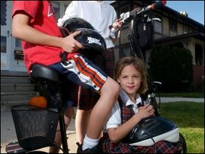 Zachary, Jackie, and Mackenzie Guenin, from left, are enthusiastic about the battery-powered scooter their dad bought a week ago to help them get around their South Toledo neighborhood efficiently. But police point out that it's illegal to ride the scooters on sidewalks.
