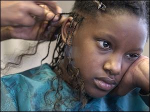 Michelle Holmes, 9, waits patiently as Lashawnda Horton braids her hair at Divas and Gents on Lagrange Street.