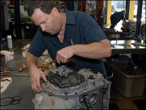 Ernie Burgess rebuilds a transmission at Cottman Transmission Center at 5230 Airport Highway. The center is close to being the second largest of 385