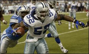 Dallas' Dexter Coakley (52) tries to shed Detroit's Ray Brown following an interception.