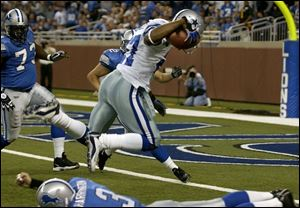 Dallas cornerback Mario Edwards leaps over the Lions' Joey Harrington en route to a TD after an interception.