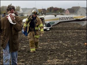 Dr. Richard Munk of Sylvania walks away from his plane with a broken nose after he made a forced landing in a field.