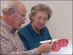 Toledo seniors Francis and Melva Fry look over literature during a driving course at MCO's Collier Building.