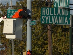 Dave Durfey installs a larger, more reflective road sign at the Holland-Sylvania and Sylvania Avenue intersection. Crews are replacing signs throughout Lucas County to help combat failing eyesight for seniors and other drivers.