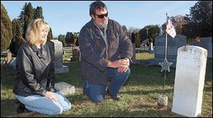 Sandy Komisarek and Bill Tunison, cemetery co-sextons, visit the grave of John Pelkey, a civil war veteran, in Springfield Township Cemetery.