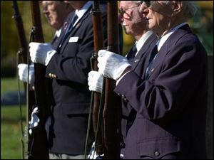 Members of the Lucas County Burial Corps wait to perform a military salute during a funeral at Calvary Cemetary.