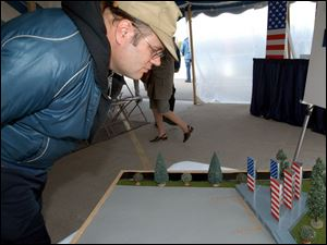 Jeff Exton, who works at the Lima Army Tank Plant, views a model of the monument to be built outside the plant. Officials hope to have it completed by Veterans Day next year.