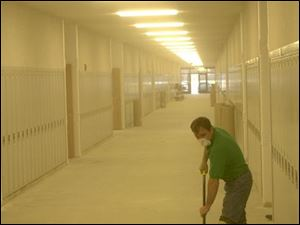 Shop foreman Rick Jackson is engulfed in dust as he sweeps a hallway of the new Gibsonburg High School before the floor is put down. Students are scheduled to move in after the Christmas break.