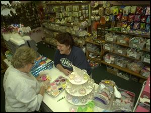 Pam Hovey, left, assists Sandy Cutcher select cake decorations at Cake Arts Supplies, 2858 West Sylvania Ave.