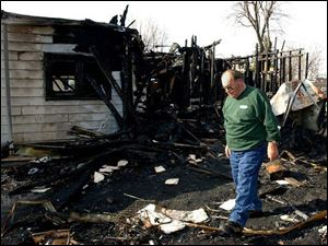 Richard Rickard picks through the rubble of his home in Leipsic in search of personal effects that survived the fire.