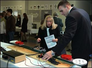 Debbie Whitcum of Elmore,OH listens to Nathan Rose as he explains how the Reverse Guiding System works during the Senior Design Engineering Project Exposition at the University of Toledo College of Engineering. Lisa dutton 12/12/2003 CTY design12p 1