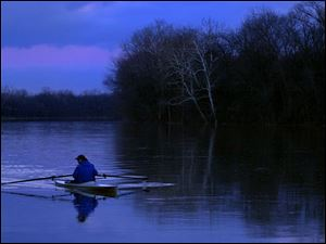 ROV RIVER 1. Neirel Bernblum (cq) rows up the Maumee River by Fransworth Metropark as cold settels in just after sunset on Friday evening.  Bernblum has been rowing on the river for over 20 years.  Lucas Mobley / The Blade