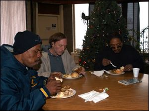 From left, Keith Purifie, Denny Bocian, and Michael Welch share a meal at Just As I Am Christian Church in downtown Toledo on Madison Avenue.