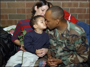 Sgt. Donnale Williams kisses Donnale, Jr., 2, as his wife Katherine and son Christopher, 11 (partially hidden), look on during a ceremony at Owens Community College yesterday for departing members of the 216th Engineer Battalion, Company C. Sergeant Williams departs for the Middle East later this month.