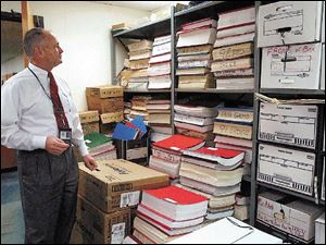 Mayor John Quinn surveys boxes and stacks of records in the copy machine room at Bowling Green City Hall. Documents for the personnel, finance, and mayor s offices are stored in the room.