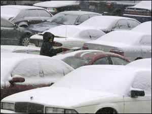 A women cleans snow from her car in a downtown Toledo parking lot before venturing out on slippery roads.