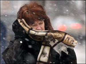 Eileen Hoye battles the wind and blowing snow as she heads back to work after lunch in downtown Toledo.