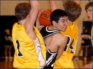 Otsego's Damien Montelongo, center, tries to squeeze through Woodmore's David Bowen, left, and Nick Arndt.