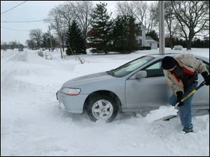 Perrysburg High School sophomore Conrad Seiling digs his car out of his driveway along Five Point Road.
