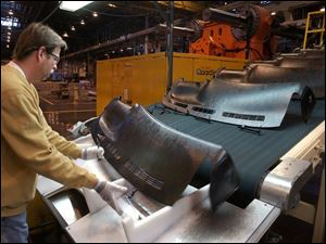 Mark Morris retrieves a component at the Adrian, Mich., Delphi plant, which is to make dashboards for two upcoming pickup-truck models.