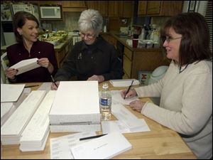 INVITATION ONLY: Cynthia Ford, left, Kathy Holmes, and Candace Morel sign, stamp, and stuff invitations in Mrs. Morel's home for Mom's Nite Out 2004.