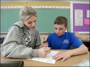 Jesica Justafson, left, works with fifth grader Devin Barnaby in Swanton Local s Park Elementary School. Voters will be asked to adopt a 1.25 percent income tax.