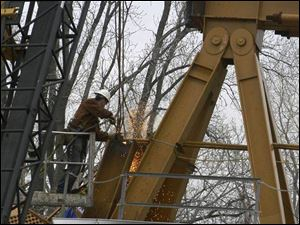 A workman cuts away a portion of the wrecked crane where four workers were killed and four others were hurt Feb. 16.