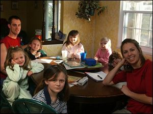 Amy Mathews, right, and her husband, Dan, left, with their daughters, clockwise: Kim, 8; Molly, 7; Heidi, 10; Hannah, 6; Olivia, 3; and Brittany, 4, at their Northwood home.