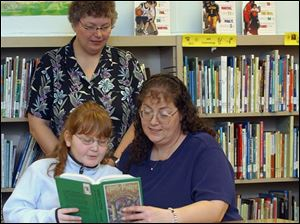 Sarah Sager, with mother Cari, had trouble reading, but now likes to read. Facilitator Cindy Kline listens.