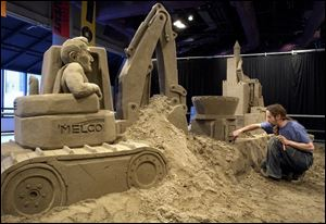 SPT March 28, 2004 - Sand artist Carl Jara of Cleveland creates a one of a kind sand sculpture featuring local construction suppliers and businesses for the Sandsational Science spring break event to be held at COSI April 3-18.  The featured sponsoring businesses are Kuhlman Corp., Melco Inc., and Miller Brothers Construction.  Blade photo by Dave Zapotosky
