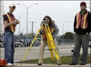 ROV March 29, 2004 - University of Toledo civil engineering students, l-r, Jeremiah Cedoz, Amanda Moore, and Eric Barbour, take measurements with a level during a surveying class field exercise outside the engineering building Monday afternoon.  Blade photo by Dave Zapotosky