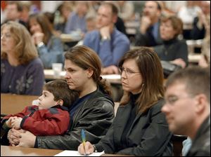 Aleca Kamilaris, son Andreas, 5, and friend Trudy Cox hear the new plan, in which Andreas will stay at Highland Elementary.