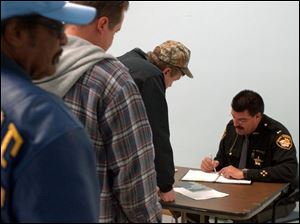 Lt. Greg Wojciechowski hands out applications in Lucas County yesterday to applicants for carry permits.