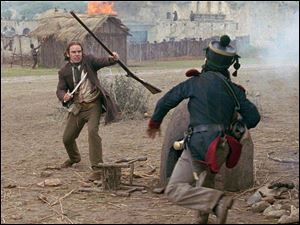 Davy Crockett (Billy Bob Thornton), left, fights off a Mexican soldier in The Alamo.