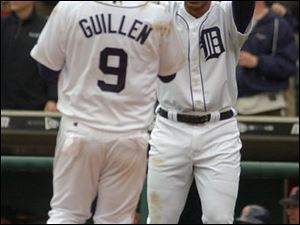 Carlos Guillen is greeted at the plate by Carlos Pena after scoring a run. The 4-0 Tigers battled back from a 3-0 deficit for an easy victory.