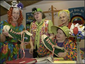 Gloria Parker (left) and Ruby Burkey hold size 18 shoes that belong to Yuk Yuk the clown, who will be part of their Bright Sunday celebration. Donna Mohn (back left) and JoAnn Diefenthalaer look on.