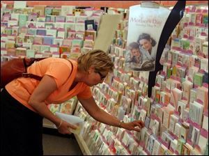 Like many another shopper just before Mother's Day, Lori Zientara Edgeworth, of Toledo, looks over a selection of cards, at Gen's Hallmark Store in Westgate Shopping Center.