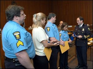 Toledo Police Chief Michael Navarre, right, honors Officer Shelli Kilburn, as Sgt. Edward Mohr, left, and Officers Brenda Sarahman and Thomas Corser look on. The latter three officers were honored for coming to the aid of Officer Kilburn, who had been shot on Feb. 26.