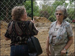 Gaye Gindy, left, and Jackie Konwinski spent time yesterday at the site of the Lathrop House. Behind them is what's left of the basement where runaway slaves reportedly hid.