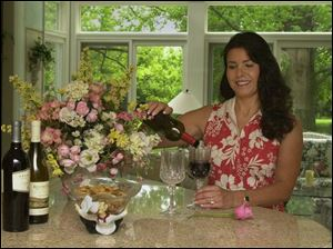 Nancy Klewer pours wine for guests as she prepares for a party.